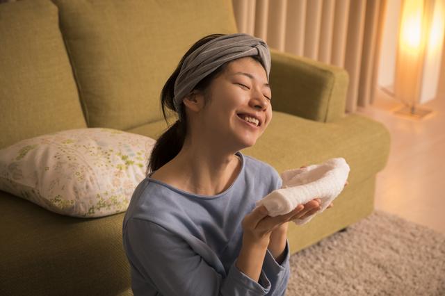 蒸しタオルで目を温める女性