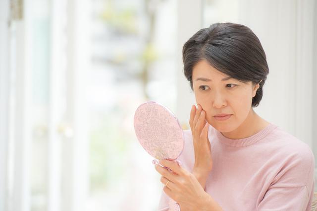肌を気にする中年の女性