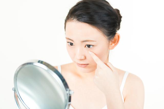 鏡で目を調べる女性