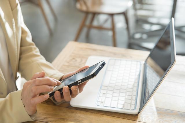 パソコンとスマホを使用している女性