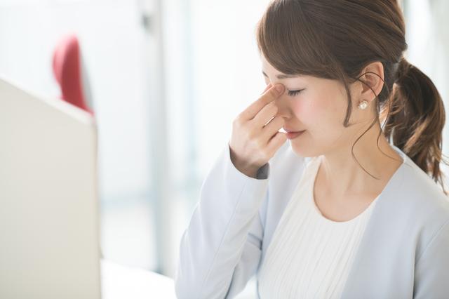 目の疲れを感じる女性
